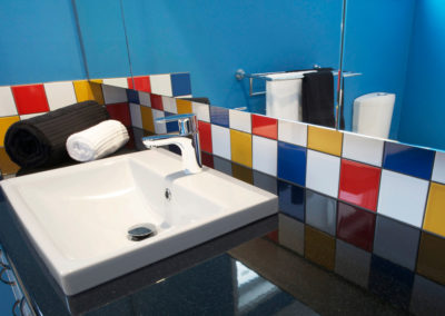 MAIN-bathroom-bright-blue-red-yellow-primary-colours-black-laminate-vanity-top-sink-kitchen-update