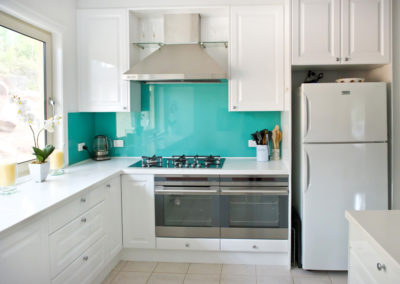 MAIN-polytec-white-gloss-argentina-aqua-rockpool-glass-splashback-electrolux-double-ovens-qasair-canopy-rangehood-corian-kitchen-update-2