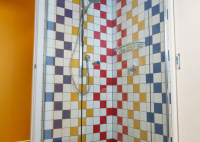 bathroom-bright-blue-red-yellow-primary-colours-black-white-tiles-pattern-shower-kitchen-update